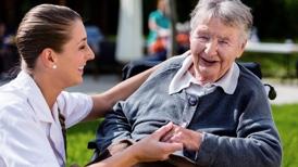 Krankenpflegerin lacht mit einer alten Dame im Rollstuhl