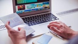 Buchung von Reiseversicherung mit Laptop und Ausweis