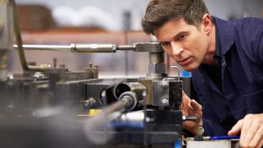 Handwerker beim Beobachten und Prüfen einer Maschine