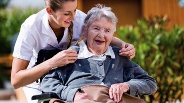 Pflegekraft unterstützt ältere Dame im Rollstuhl