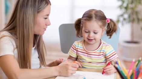 Au-Pair zeichnet Bild mit kleinem Mädchen
