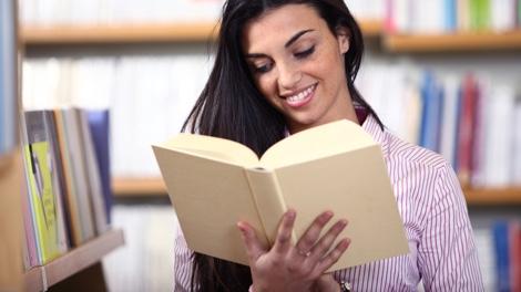 Studentin ließt Buch in Bibliothek