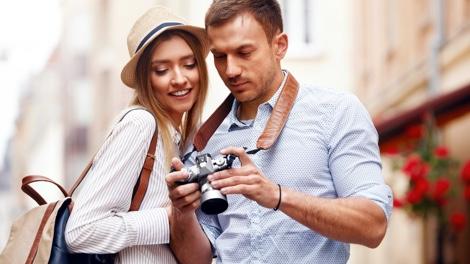 Mann und Frau als Touristen betrachten Fotos auf Kamera