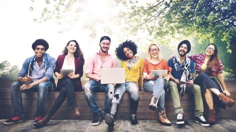 Gruppe von jungen Erwachsenen sitzend auf einer Bank