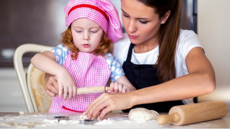 Au pair baking with a little girl in a checked apron