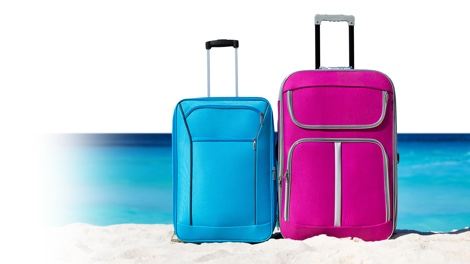 Small blue suitcase and big suitcase in pink at the beach