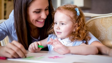 Au pair painting and laughing with red-haired girl