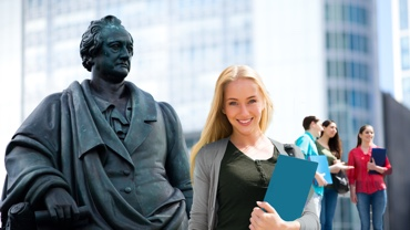 Woman with blue document folder in front of Goethe statue