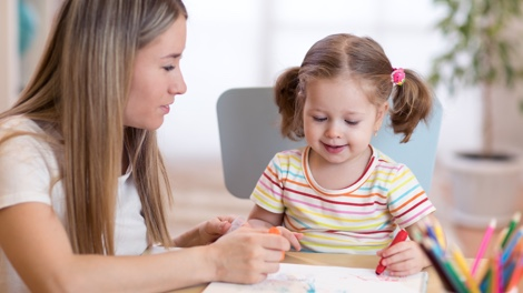 Au pair draws picture with little girl